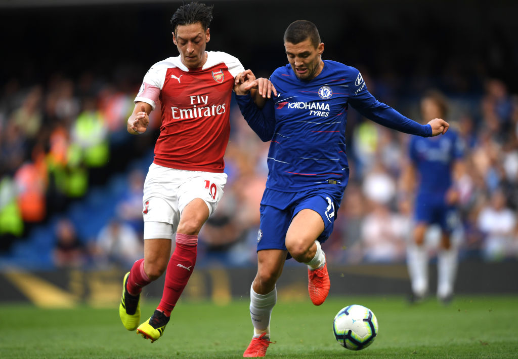 LONDON, ENGLAND - AUGUST 18: Mesut Ozil of Arsenal battles for possession with Mateo Kovacic of Chelsea during the Premier League match between Chelsea FC and Arsenal FC at Stamford Bridge on August 18, 2018 in London, United Kingdom. (Photo by Shaun Botterill/Getty Images)