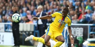 HUDDERSFIELD, ENGLAND - SEPTEMBER 15: Wilfried Zaha of Crystal Palace is fouled by Mathias Zanka Jorgensen of Huddersfield Town during the Premier League match between Huddersfield Town and Crystal Palace at John Smith's Stadium on September 15, 2018 in Huddersfield, United Kingdom. (Photo by Nigel Roddis/Getty Images)