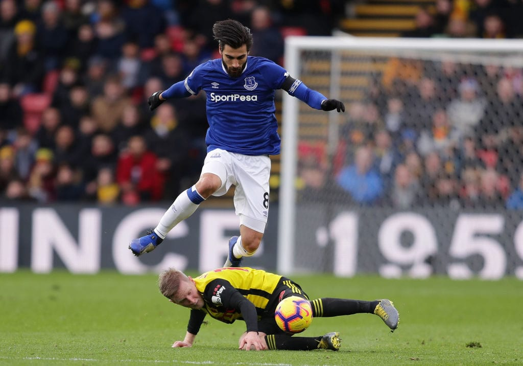 WATFORD, ENGLAND - FEBRUARY 09: Andre Gomes of Everton skips over Will Hughes of Watford during the Premier League match between Watford FC and Everton FC at Vicarage Road on February 9, 2019 in Watford, United Kingdom. (Photo by Richard Heathcote/Getty Images)