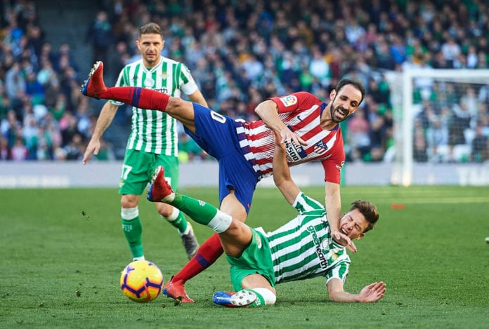 SEVILLE, SPAIN - FEBRUARY 03: Juanfran Torres of Club Atletico de Madrid (L) competes for the ball with Francisco Javier Guerrero