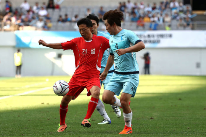 SEOUL, SOUTH KOREA - AUGUST 11: Players from South Korea (blue) and North Korea (red) compete for the ball during a