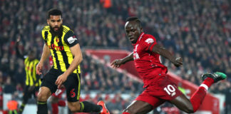 LIVERPOOL, ENGLAND - FEBRUARY 27: Sadio Mane of Liverpool shoots under pressure from Adrian Mariappa of Watford during the Premier League match between Liverpool FC and Watford FC at Anfield on February 27, 2019 in Liverpool, United Kingdom. (Photo by Clive Brunskill/Getty Images)