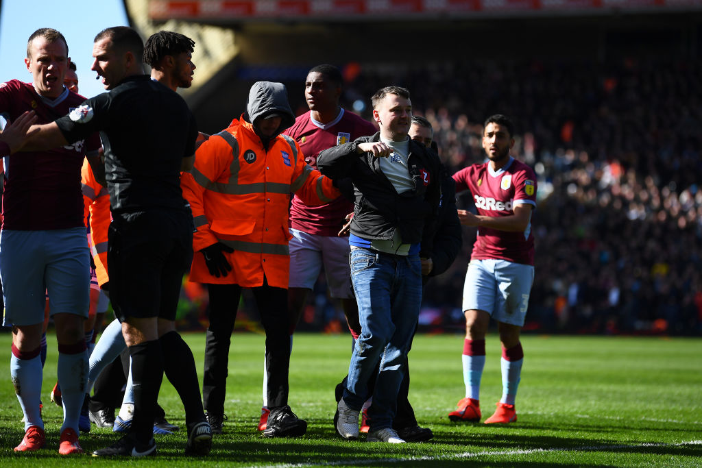 BIRMINGHAM, ENGLAND - MARCH 10: A fan is escorted off the pitch after striking Jack Grealish of Aston Villa during the Sky Bet Championship match between Birmingham City and Aston Villa at St Andrew's Trillion Trophy Stadium on March 10, 2019 in Birmingham, England. (Photo by Alex Davidson/Getty Images)