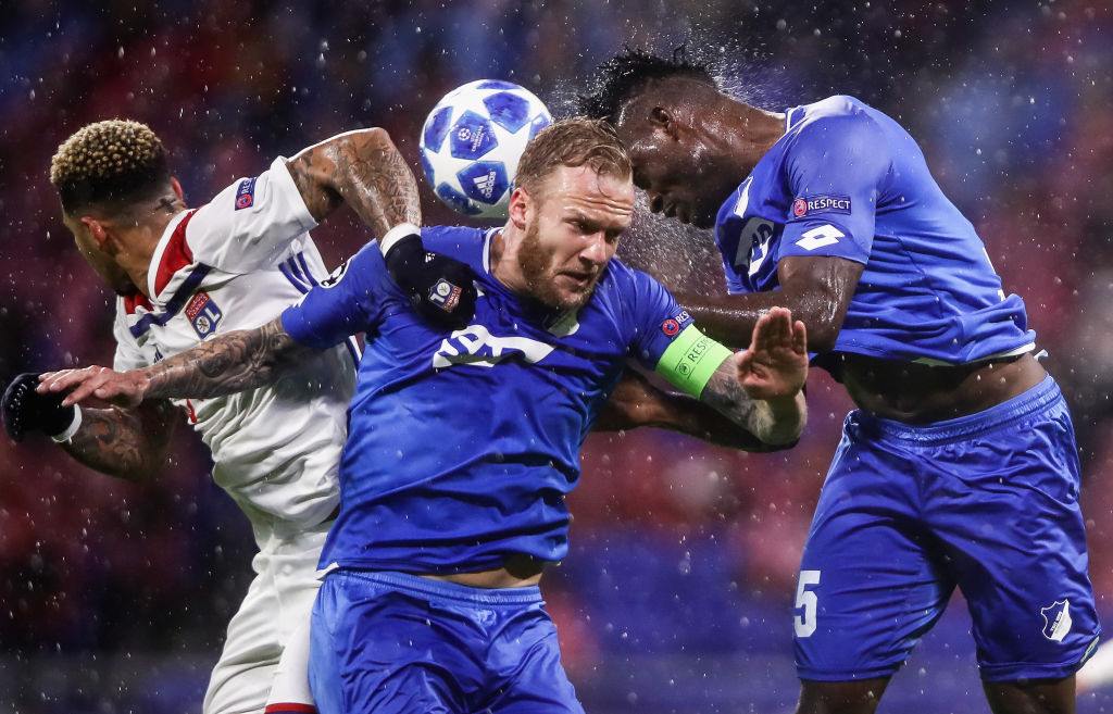 LYON, FRANCE - NOVEMBER 07: Memphis Depay of Lyon jumps for a header with Kevin Vogt and Kasim Adams Nuhu (L-R) of Hoffenheim during the Group F match of the UEFA Champions League between Olympique Lyonnais and TSG 1899 Hoffenheim at Groupama Stadium on November 7, 2018 in Lyon, France. (Photo by Alex Grimm/Getty Images)