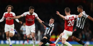 LONDON, ENGLAND - APRIL 01: Miguel Almiron of Newcastle United is tackled by Sokratis Papastathopoulos and Shkodran Mustafi of Arsenal during the Premier League match between Arsenal FC and Newcastle United at Emirates Stadium on April 01, 2019 in London, United Kingdom. (Photo by Catherine Ivill/Getty Images)
