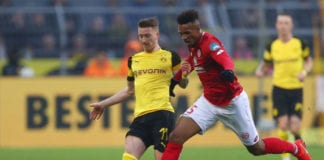 DORTMUND, GERMANY - APRIL 13: Marco Reus of Borussia Dortmund holds off Jean-Philippe Gbamin of FSV Mainz during the Bundesliga match between Borussia Dortmund and 1. FSV Mainz 05 at Signal Iduna Park on April 13, 2019 in Dortmund, Germany. (Photo by Lars Baron/Bongarts/Getty Images)