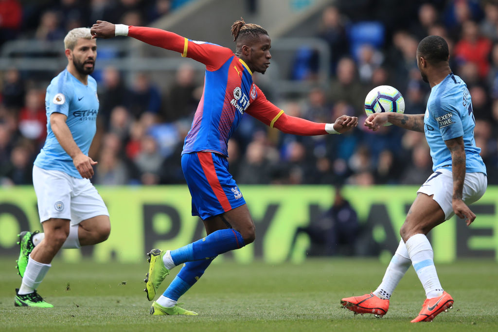 LONDON, ENGLAND - APRIL 14: Wilfried Zaha of Crystal Palace takes on Raheem Sterling and Sergio Aguero of Manchester City during the Premier League match between Crystal Palace and Manchester City at Selhurst Park on April 14, 2019 in London, United Kingdom. (Photo by Marc Atkins/Getty Images)