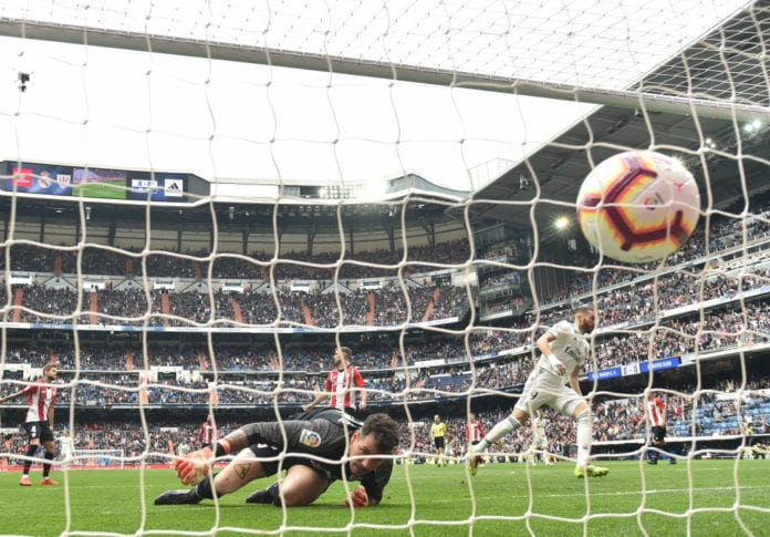 MADRID, SPAIN - APRIL 21: Karim Benzema of Real Madrid CF beats Iago Herrerin of Athletic Club to score Real's first goal during the La Liga match between Real Madrid CF and Athletic Club at Estadio Santiago Bernabeu on April 21, 2019 in Madrid, Spain. (Photo by Denis Doyle/Getty Images)
