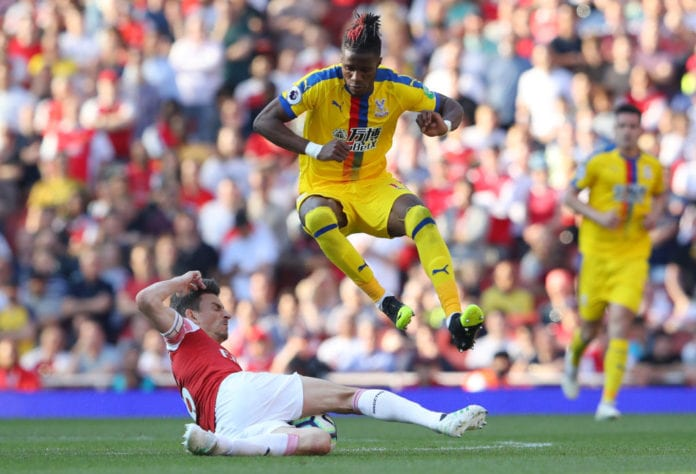 LONDON, ENGLAND - APRIL 21: Laurent Koscielny of Arsenal tackles Wilfried Zaha of Crystal Palace during the Premier League match between Arsenal FC and Crystal Palace at Emirates Stadium on April 21, 2019 in London, United Kingdom. (Photo by Warren Little/Getty Images)