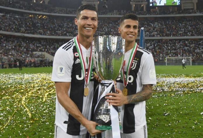 JEDDAH, SAUDI ARABIA - JANUARY 16: Joao Cancelo and Cristiano Ronaldo of Juventus celebrate after winning the Italian Supercup match between Juventus and AC Milan at King Abdullah Sports City on January 16, 2019 in Jeddah, Saudi Arabia. (Photo by Claudio Villa/Getty Images for Lega Serie A)
