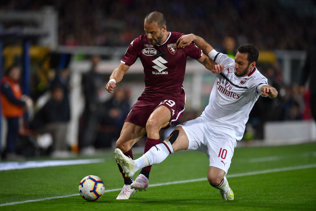 TURIN, ITALY - APRIL 28: Lorenzo De Silvestri (L) of Torino FC is tackled by Hakan Calhanoglu of AC Milan during the Serie A match between Torino FC and AC Milan at Stadio Olimpico di Torino on April 28, 2019 in Turin, Italy. (Photo by Valerio Pennicino/Getty Images)