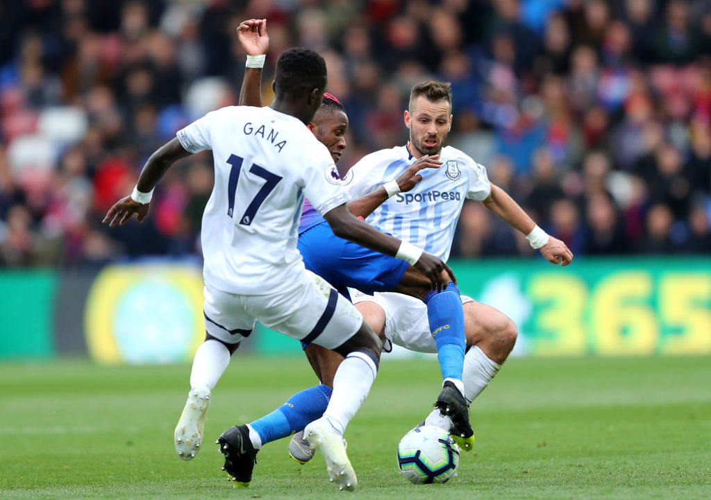 LONDON, ENGLAND - APRIL 27: Wilfried Zaha of Crystal Palace is tackled by Morgan Schneiderlin and Idrissa Gueye of Everton during the Premier League match between Crystal Palace and Everton FC at Selhurst Park on April 27, 2019 in London, United Kingdom. (Photo by Warren Little/Getty Images)