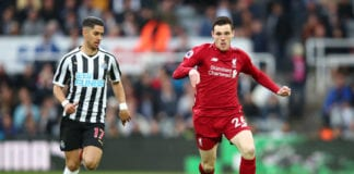 NEWCASTLE UPON TYNE, ENGLAND - MAY 04: Andy Robertson of Liverpool runs with the ball under pressure from Ayoze Perez of Newcastle United during the Premier League match between Newcastle United and Liverpool FC at St. James Park on May 04, 2019 in Newcastle upon Tyne, United Kingdom. (Photo by Clive Brunskill/Getty Images)