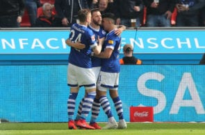 LEVERKUSEN, GERMANY - MAY 11: Guido Burgstaller of FC Schalke 04 celebrates with teammates Bastian Oczipka and Nassim Boujellab of Schalke 04 after scoring his team's first goal during the Bundesliga match between Bayer 04 Leverkusen and FC Schalke 04 at BayArena on May 11, 2019 in Leverkusen, Germany. (Photo by Christof Koepsel/Bongarts/Getty Images)