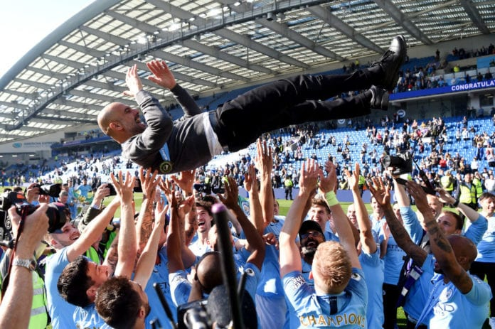 BRIGHTON, ENGLAND - MAY 12: Manchester City players throw Josep Guardiola, Manager of Manchester City in the air as they celebrate winning the Premier League title following the Premier League match between Brighton & Hove Albion and Manchester City at American Express Community Stadium on May 12, 2019 in Brighton, United Kingdom. (Photo by Mike Hewitt/Getty Images)