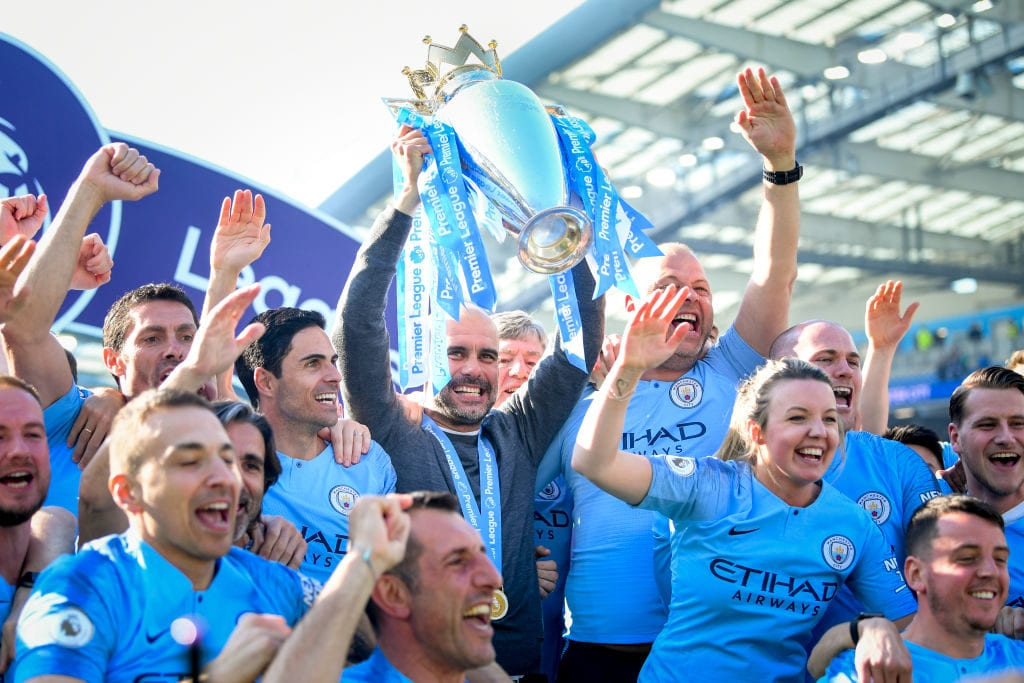 BRIGHTON, ENGLAND - MAY 12: Manchester City manager Pep Guardiola holds the Premier League trophy with backroom staff during the Premier League match between Brighton & Hove Albion and Manchester City at American Express Community Stadium on May 12, 2019 in Brighton, United Kingdom. (Photo by Michael Regan/Getty Images)