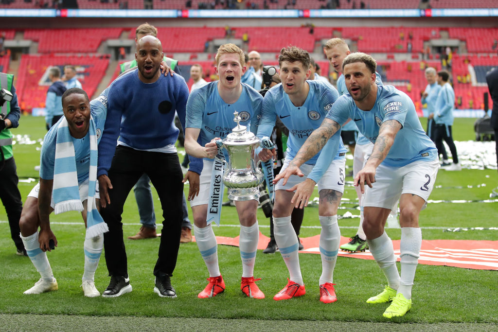 LONDON, ENGLAND - MAY 18: (L-R) Raheem Sterling, Fabian Delph, Kevin De Bruyne, John Stones and Kyle Walker of Manchester City celebrate with the trophy after winning the FA Cup Final match between Manchester City and Watford at Wembley Stadium on May 18, 2019 in London, England. (Photo by Richard Heathcote/Getty Images)