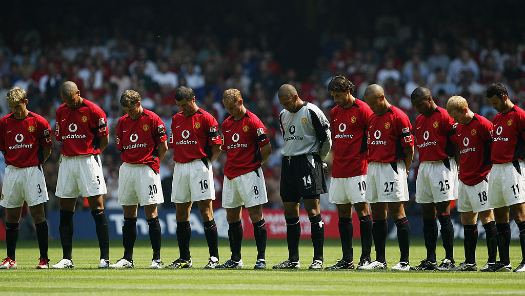 The Manchester United players stand for the minutes silence